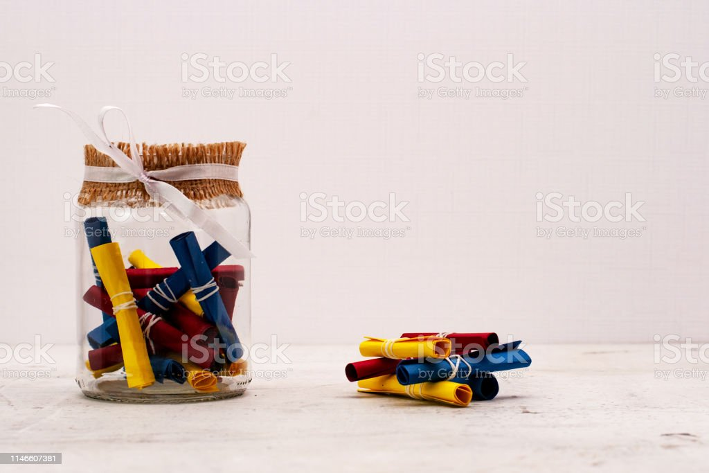 A glass jar with colored notes of craft paper. Light background