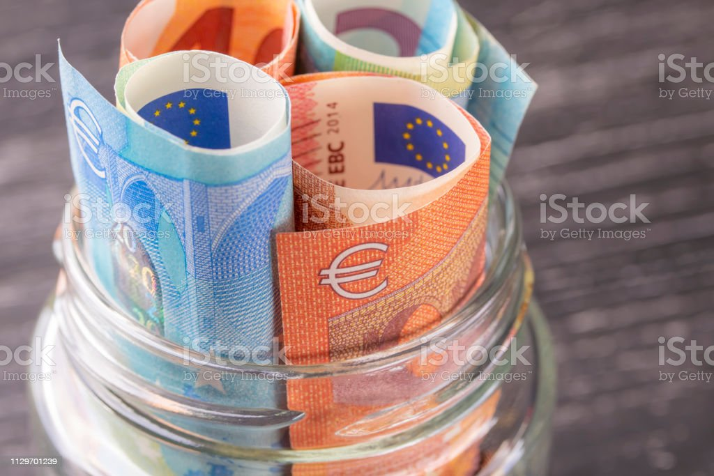 Glass jar with euro bills close-up. Glass jar with euro bills close-up. View from above. On the old black wooden table. The concept of family and personal savings. A Helping Hand Stock Photo