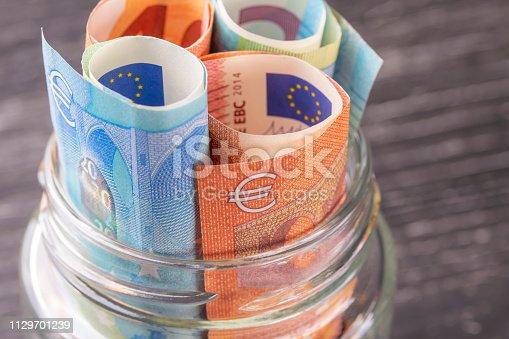 istock Glass jar with euro bills close-up. 1129701239