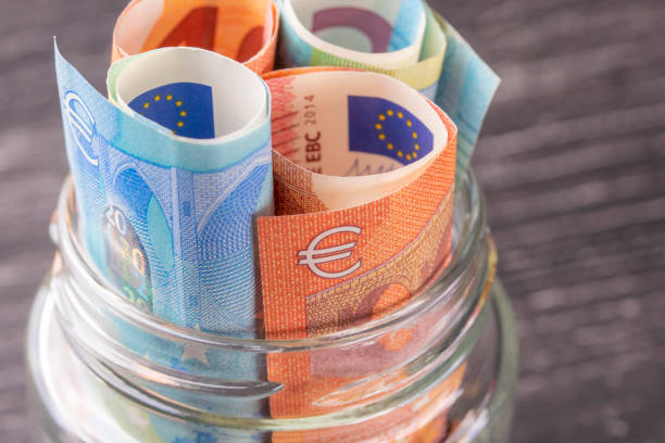 Glass jar with euro bills close-up. Glass jar with euro bills close-up. View from above. On the old black wooden table. The concept of family and personal savings. european union currency stock pictures, royalty-free photos & images