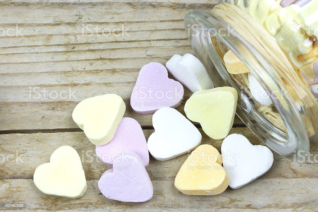 glass jar with heart candies fallen out stock photo