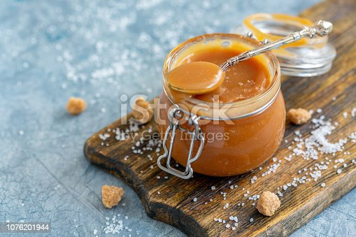 Caramel sauce with sea salt in a small jar, brown cane sugar and a spoon with salt on an old wooden serving board, selective focus.