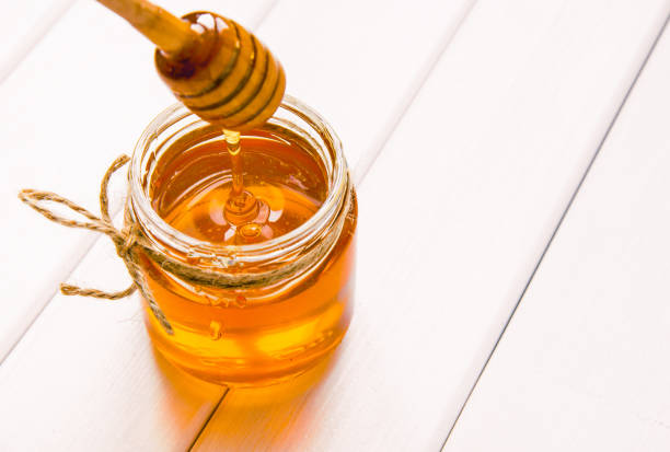 Glass jar with honey and dipper on white wooden table background stock photo
