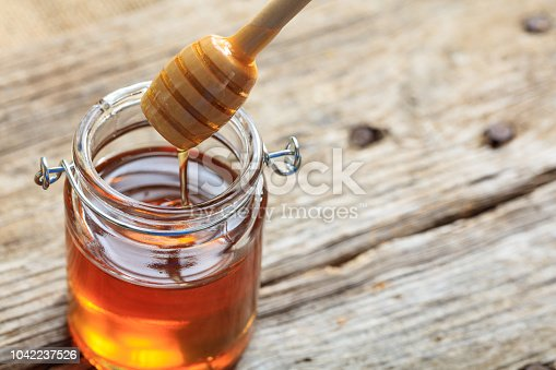 A glass jar with honey on a table