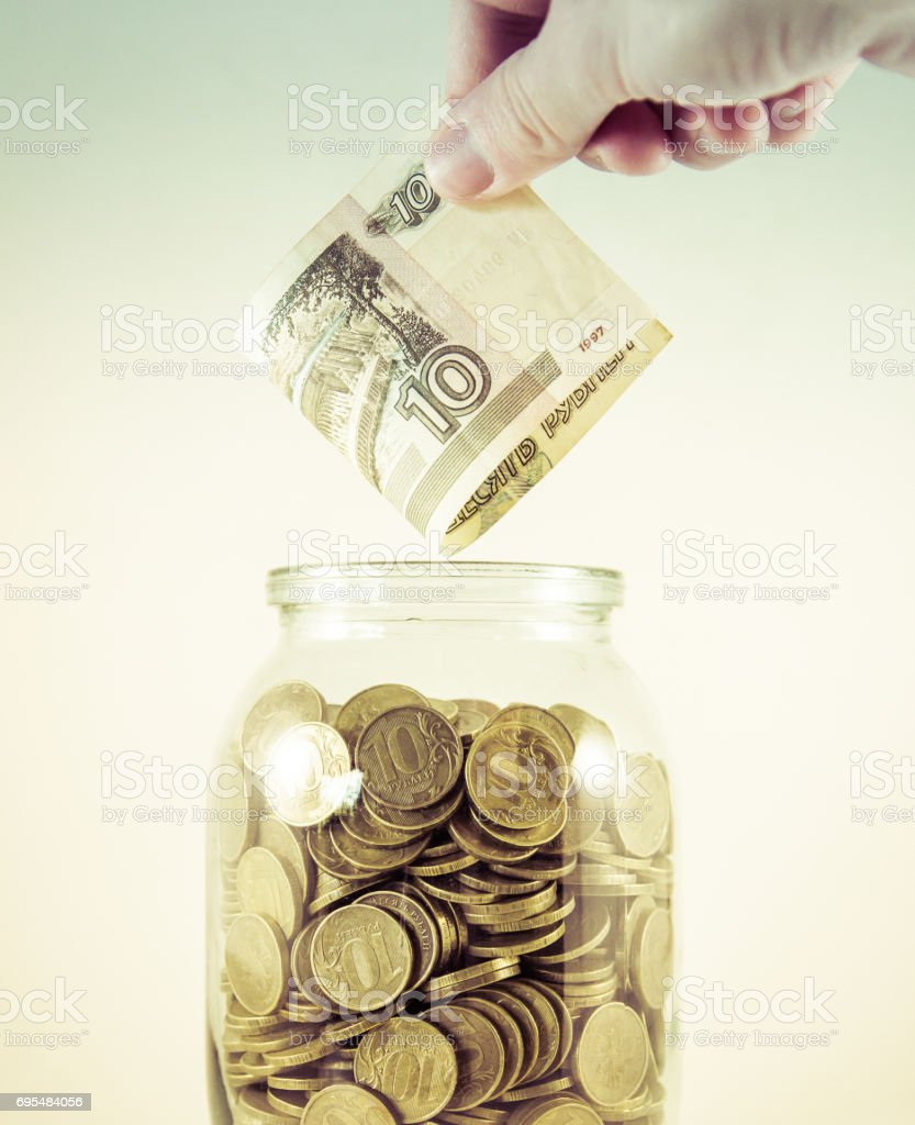Glass jar with money on a white background. Hand with money stock photo