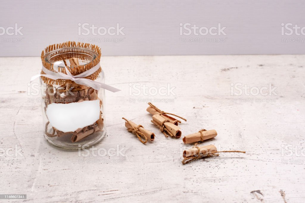 A glass jar with notes of craft paper. Light background? mock up
