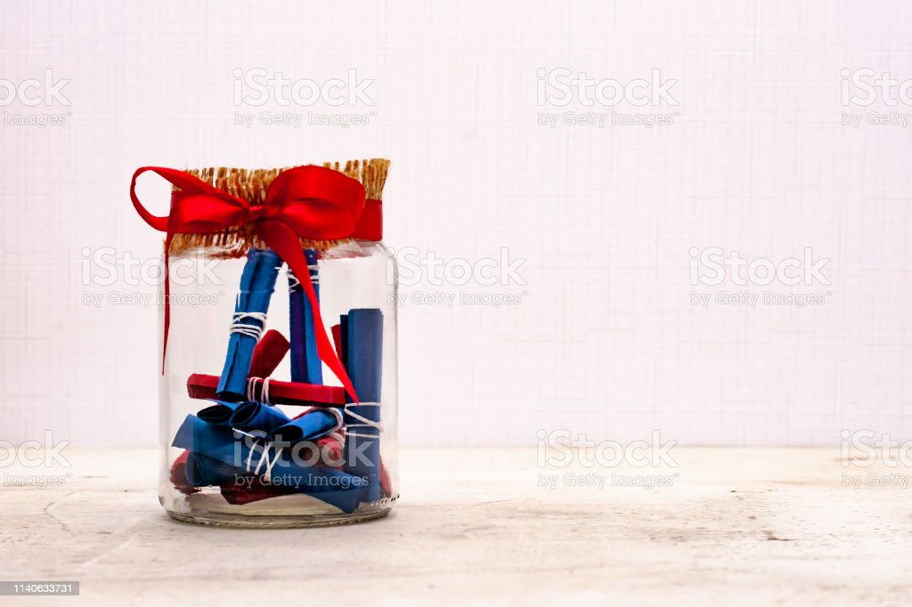A glass jar with notes of craft paper. Light background