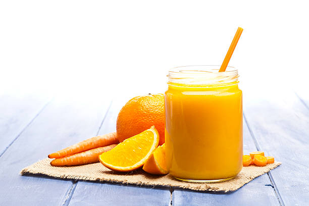 glass jar with orange and carrot juice - jus de fruit photos et images de collection