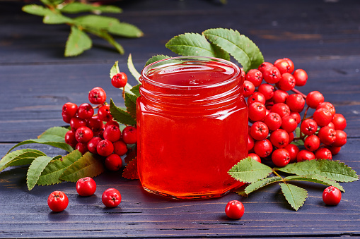 Glass jar with syrup of rowan berries on dark wooden