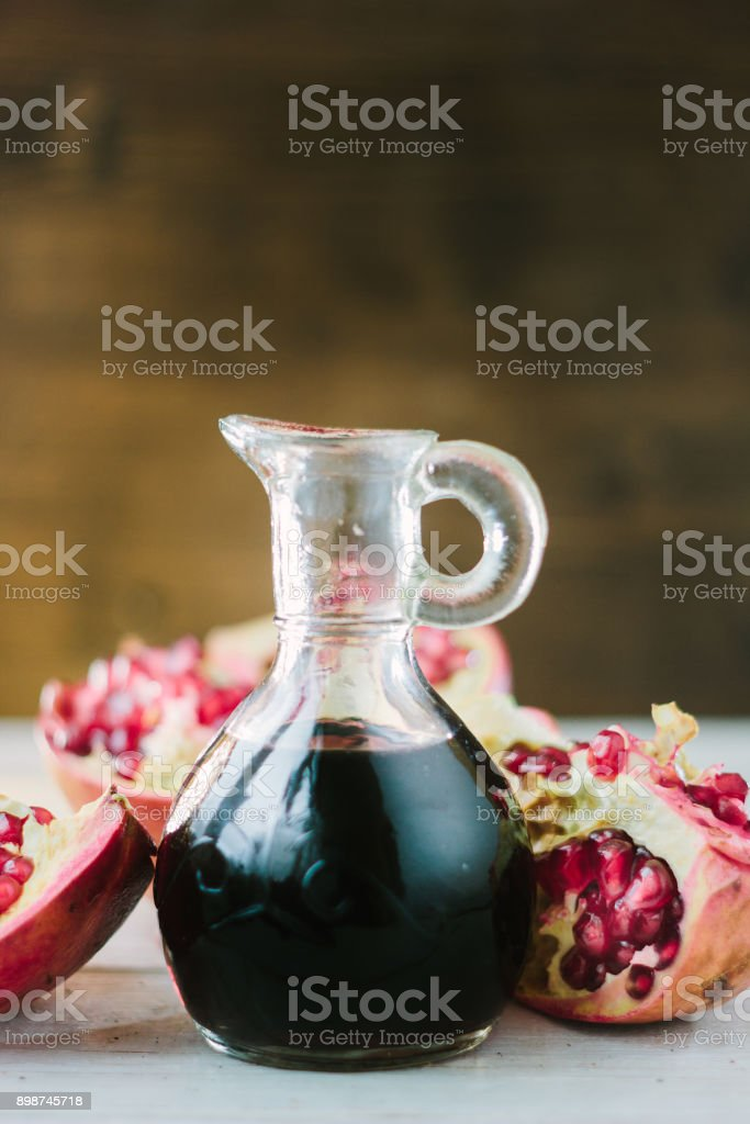 Glass jar with the pomegranate sauce inside it. stock photo