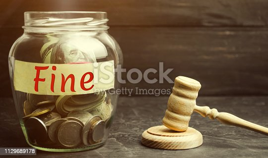 1024130248 istock photo Glass jar with the word Fine and the judge's hammer. Penalty as a punishment for a crime and offense. Financial punishment. Violations of traffic laws. Fraud. Fines can also be used as a form of tax 1129689178