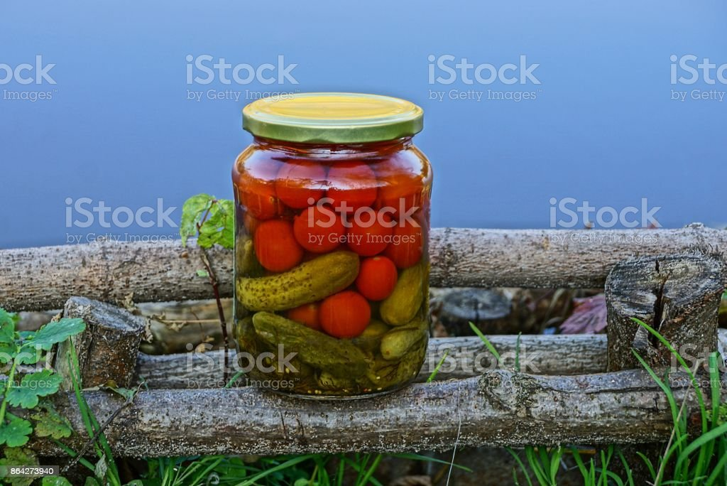 glass jar with vegetables on wooden sticks in the grass royalty-free stock photo