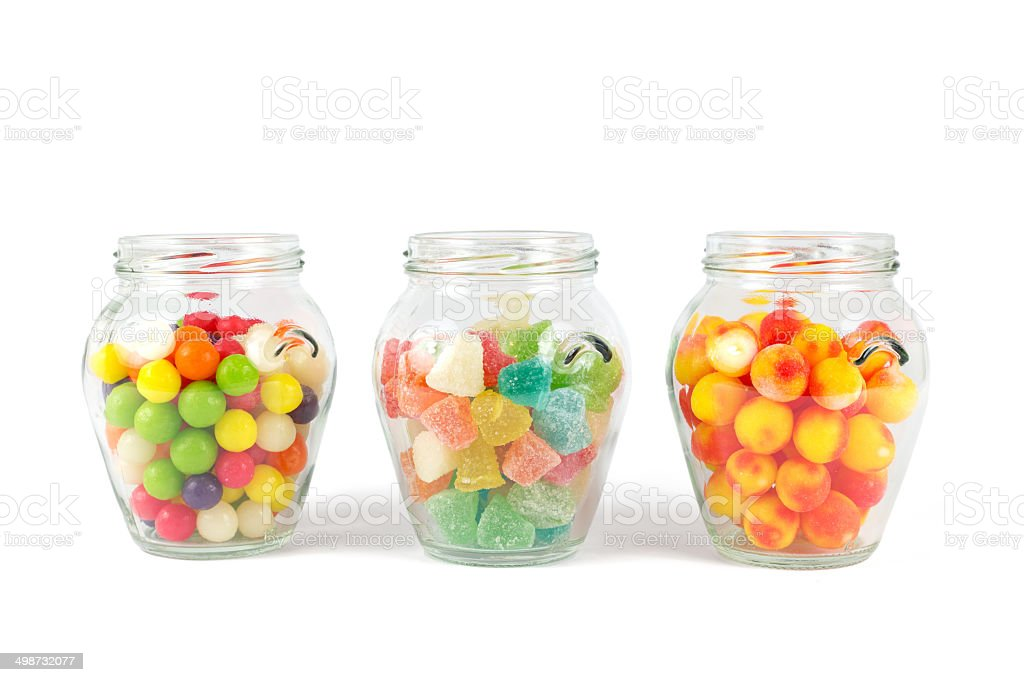 Glass jars filled with different colorful candies isolated on white stock photo