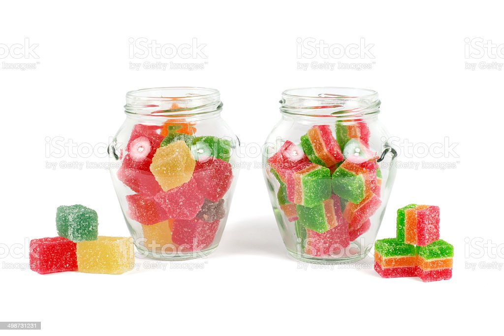 Glass jars filled with different colorful jelly isolated on white stock photo