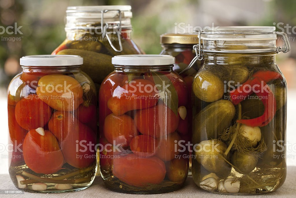 Glass jars of homemade canned tomatoes and cucumbers royalty-free stock photo