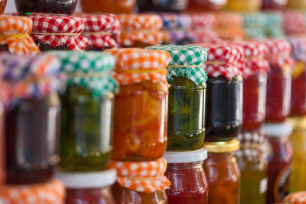 glass jars of homemade jam and marmalade for sale - jam jar imagens e fotografias de stock