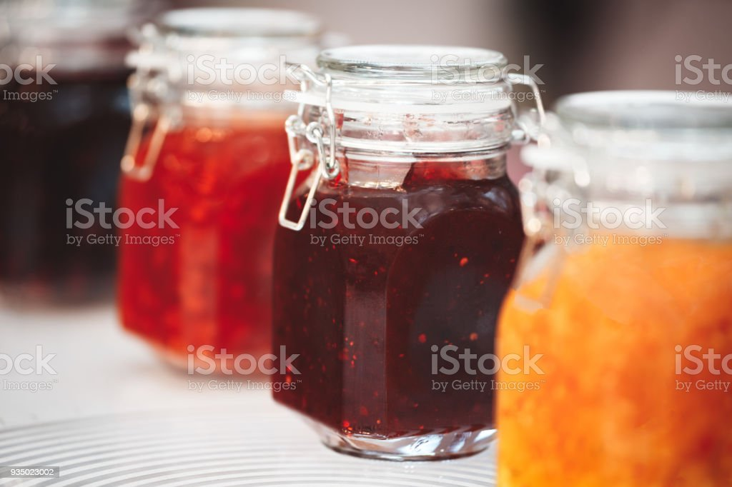Glass jars with butter, jam on the wooden shelf  on background of a dark wall, breakfast concept, kitchen background, healthy eating concept, conservation concept