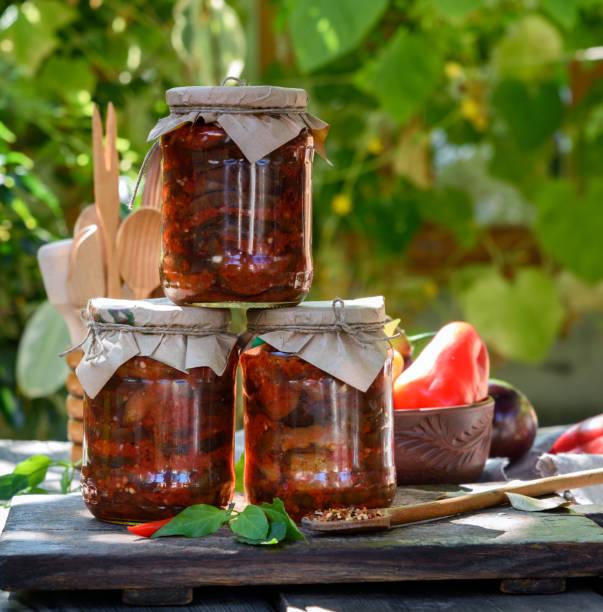 glasgläser mit konserven auberginen in gemüsesauce - peperoni stiche stock-fotos und bilder