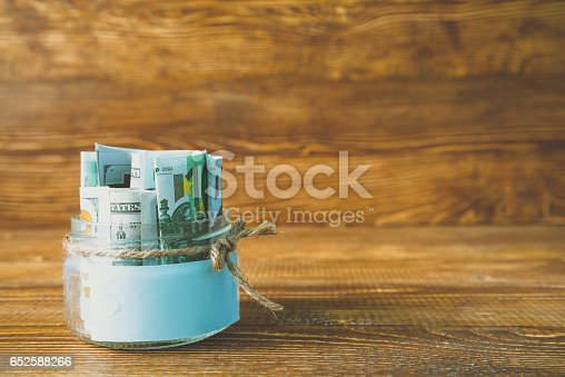 istock Glass jars with dollars and euro free space for text 652588266