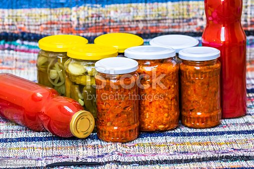 Glass jars with pickled red bell peppers and pickled cucumbers (pickles) isolated. Jars with variety of pickled vegetables, jars with zacusca and bottles with tomatoes sauce. Preserved food concept.