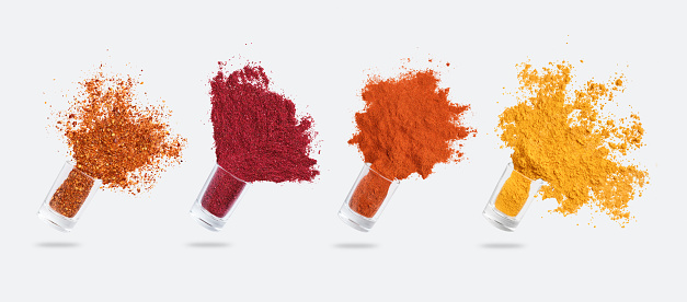 Condiments explosion. Glass jars with various spices flying isolated on white background, panorama