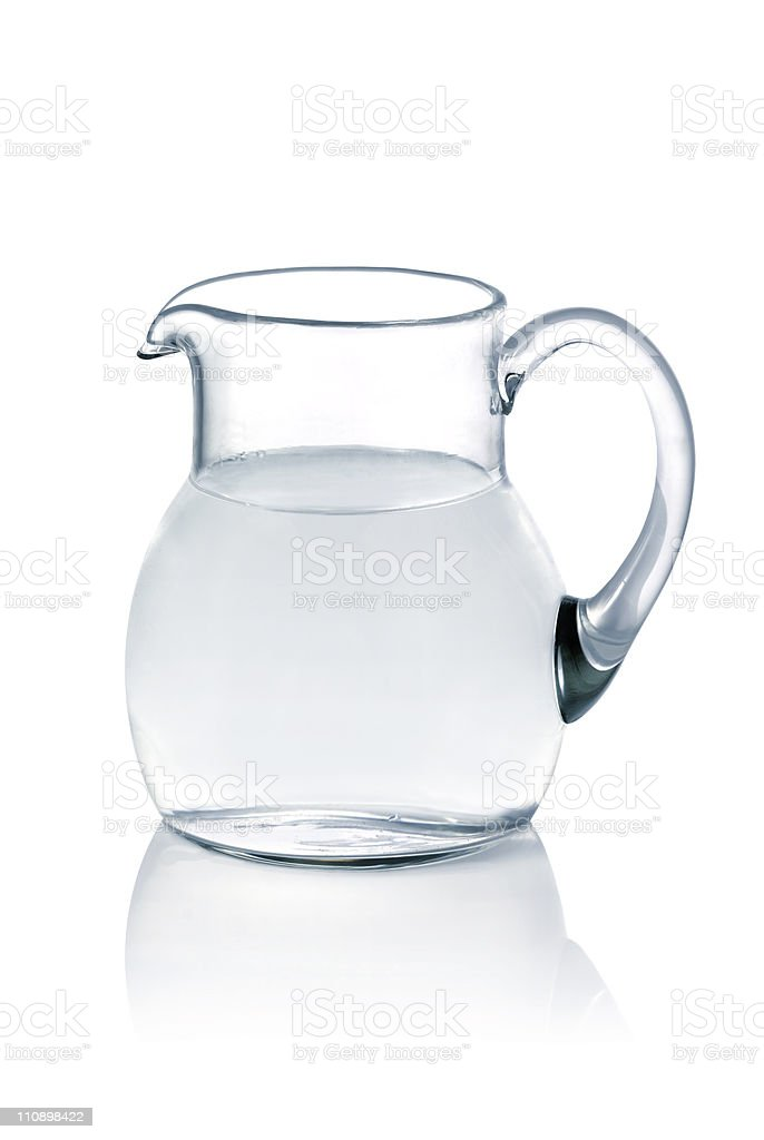 Glass jug filled with water on a white table royalty-free stock photo