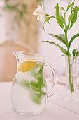 Glass jug of cold lemonade on a light background cafe. Pitcher lemon water with mint.