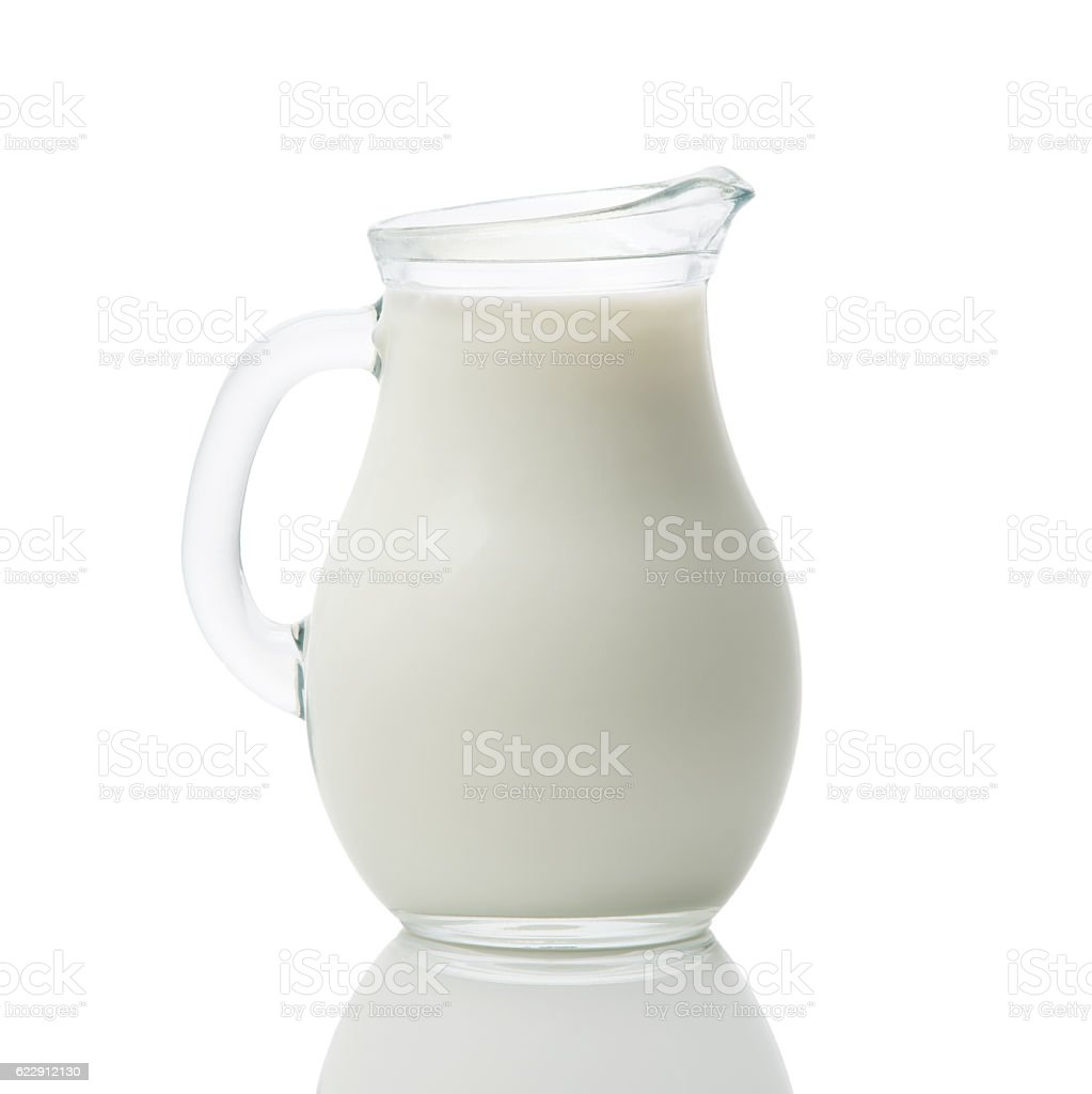 Glass jug of fresh milk isolated on white background stock photo