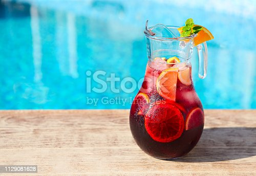 Glass jug of iced sangria with strawberry, orange, apple and lemon by the pool