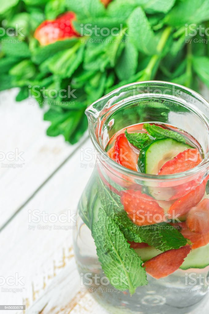 Glass Jug with Fresh Cool Infused Detox Water with Ripe Organic Strawberries Sliced Cucumbers Mint. White Plank Wood Background. Healthy Drink Detox Summer Refreshment. Copy Space stock photo