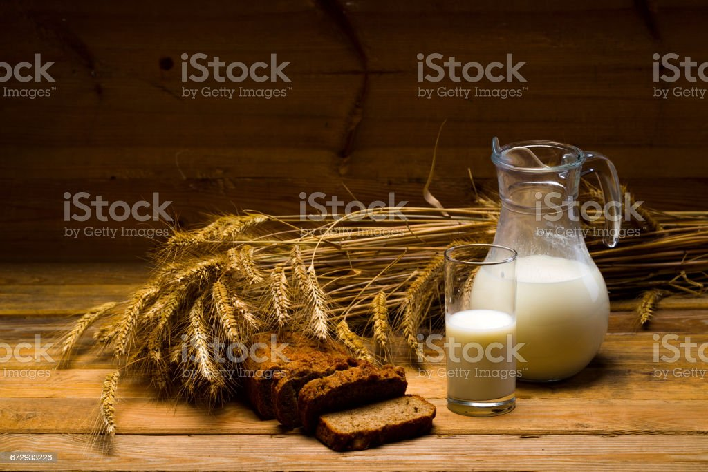 Glass jug with milk, mug with milk, a loaf of rye bread, ears stock photo