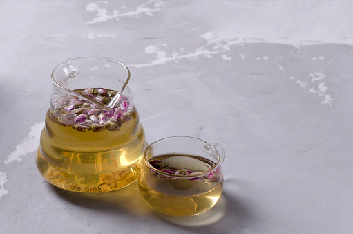A glass kettle and a small glass cup with brewed tea made of rose petals stand on a gray concrete background with a copy of the space, selective focus