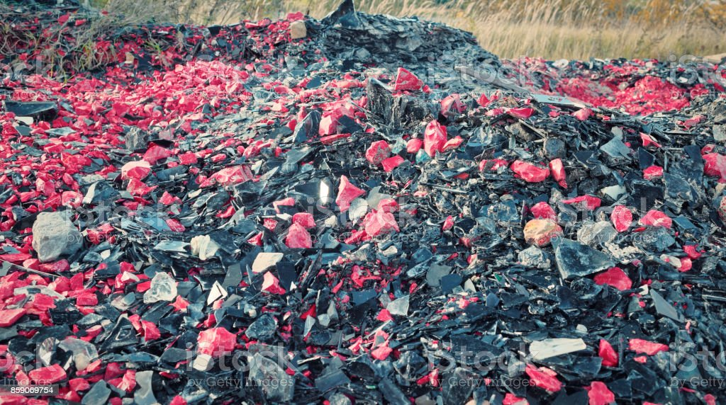 Shattered glass of red and black colors in heaps near abandoned glass...