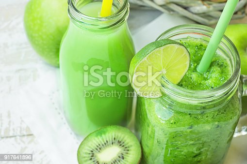 istock Glass Mason Jar and Bottle with Green Vegetable and Fruit Smoothie and Juice with Straw. Basket with Seasonal Organic Produce in Background. Spring Summer Detox 917641896