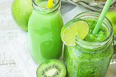 Glass Mason Jar and Bottle with Green Vegetable and Fruit Smoothie and Juice with Straw. Basket with Seasonal Organic Produce in Background. Spring Summer Detox Healthy Diet.