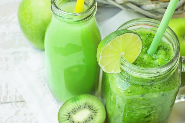 Glas-Einmachglas und Flasche mit grünem Gemüse und Obst Smoothie und Saft mit Stroh. Korb mit saisonalen Bio-Produkten im Hintergrund. Frühling-Sommer-Detox – Foto