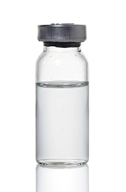 Glass medical bottle containing clear liquid  stock photo