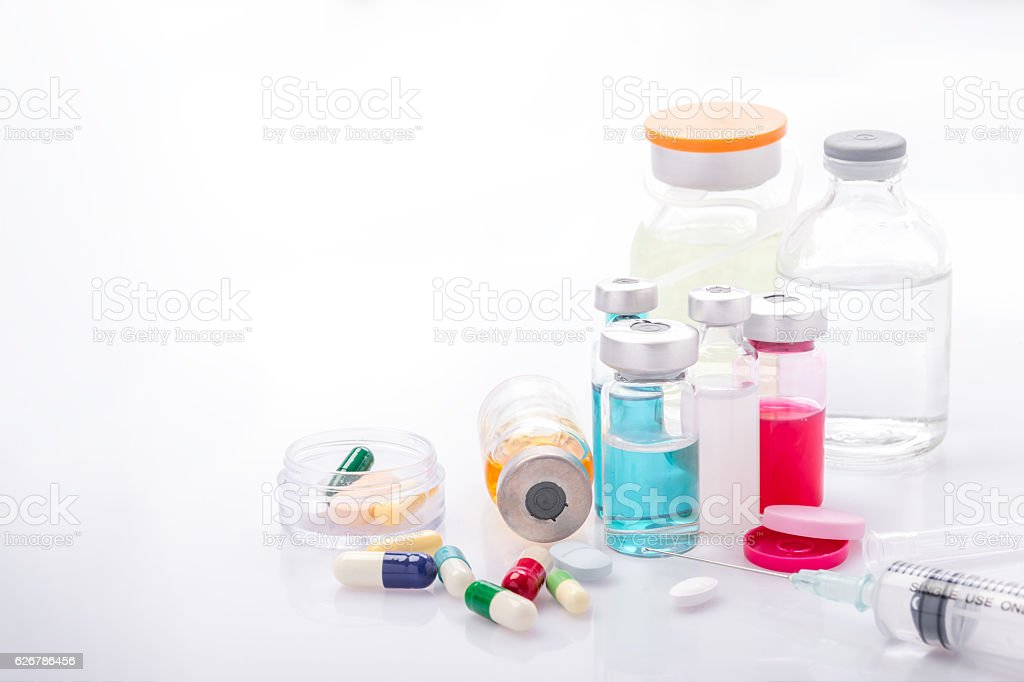 Glass Medicine Vials with syringe and pills capsule on white stock photo