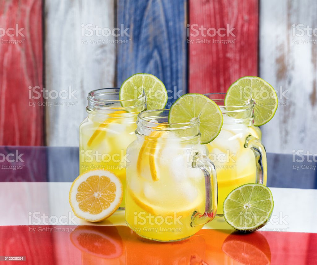 Glass mugs filled with cold lemonade on USA national colors stock photo