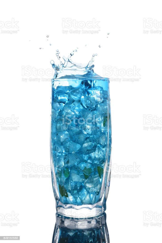 Glass of a blue alcoholic cocktail drink with ice and mint stock photo