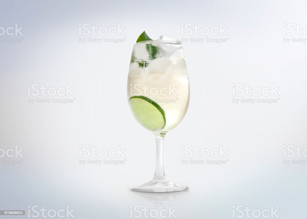 Glass of a cold cocktail drink with white wine / vermouth, slice of lemon / lime and a mint leaf. stock photo