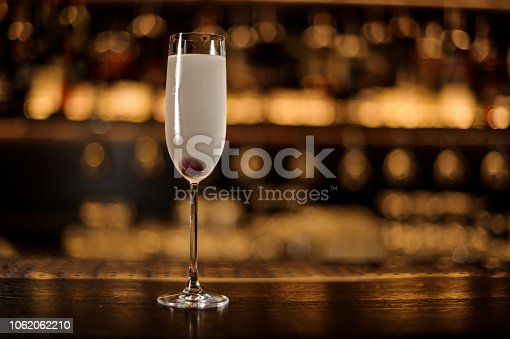 Glass of a French 75 cocktail with berry standing on the bar counter on the blurred dark and yellow light background