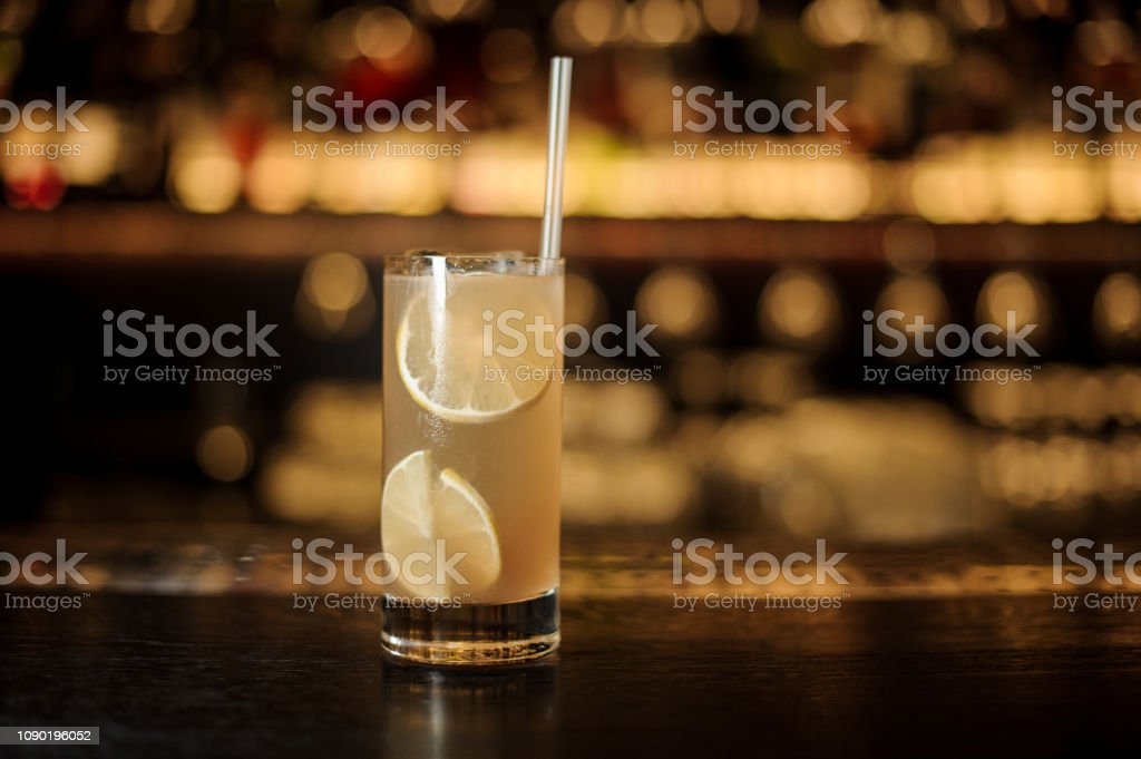 Glass of a Lemonade cocktail with oranges on the wooden bar counter stock photo