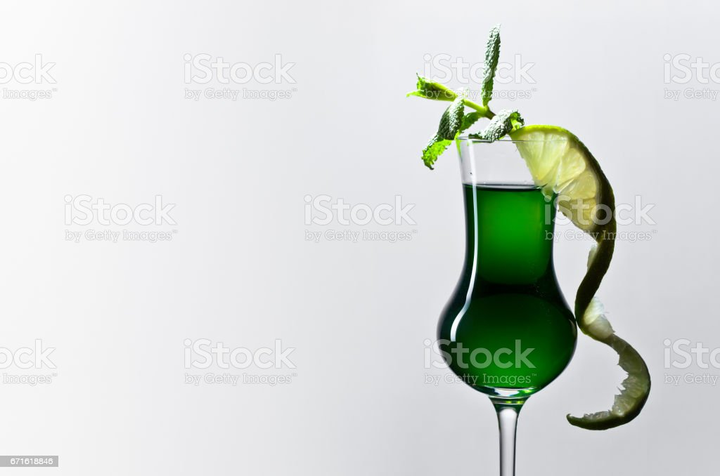 Glass of absinthe garnished with lime and mint stock photo