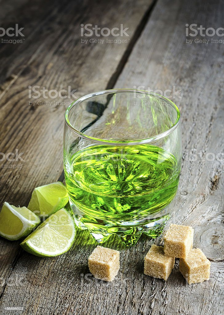 Glass of absinthe with lime and sugar cubes stock photo