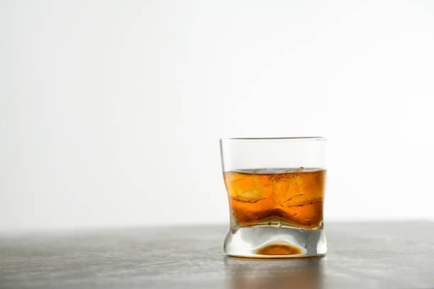 Glas gealterten goldenen Whiskey mit Eiswürfeln auf dem Tisch. Bernsteinfarbenes Alkoholgetränk mit Steinen an der Bar – Foto
