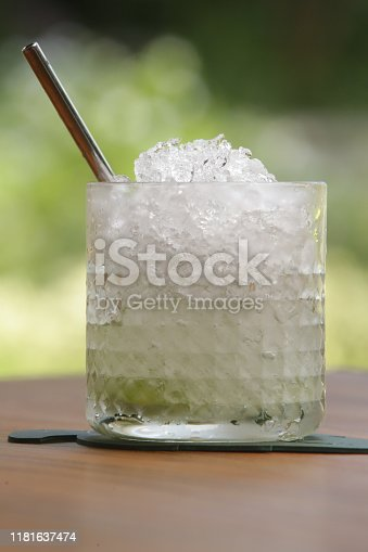 A glass of alcohol cocktail with crushed ice cubes