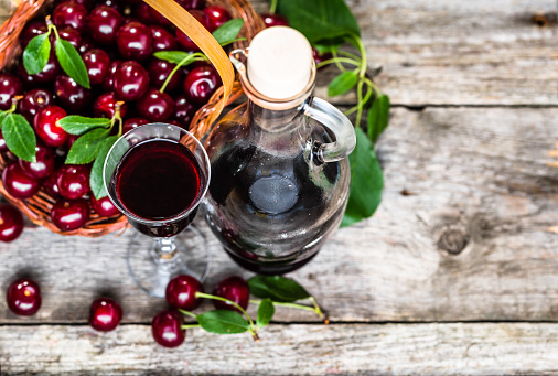 istock Glass of alcohol tincture made from cherry fruits, liquor in a bottle on rustic background 850128948