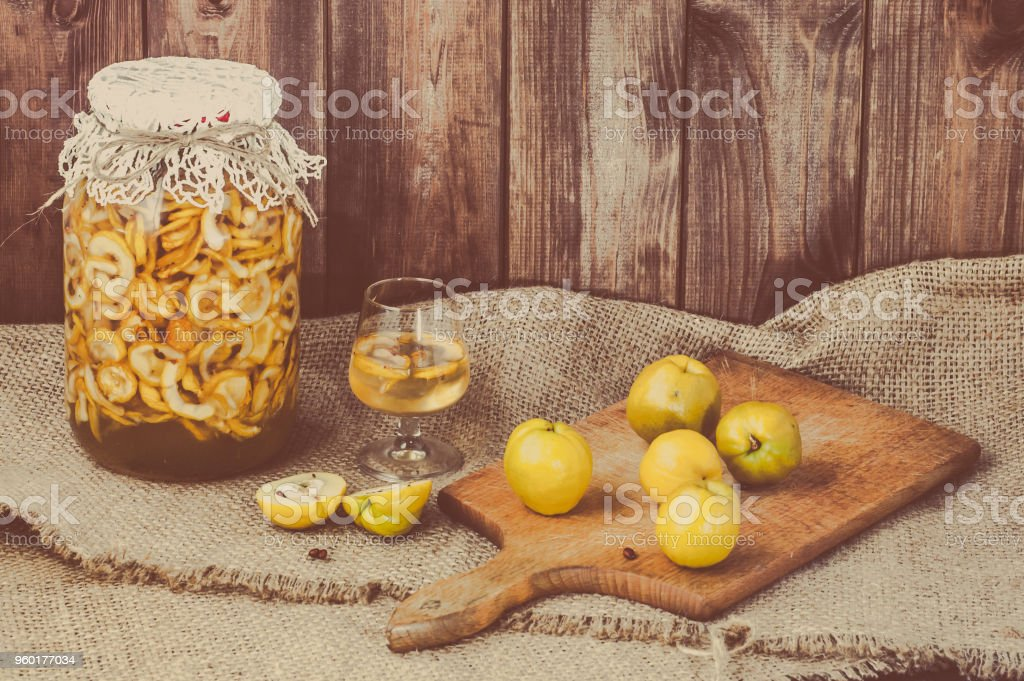 Glass of alcohol tincture made from quince fruit, liquor in a jar on rustic background, autumn preserves stock photo