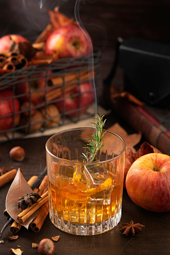Glass of alcoholic whiskey drink with a branch of rosemary with smoke and apples, cinnamon sticks. Concept of magical autumn relaxed and cozy atmosphere. Selective focus, copy space.